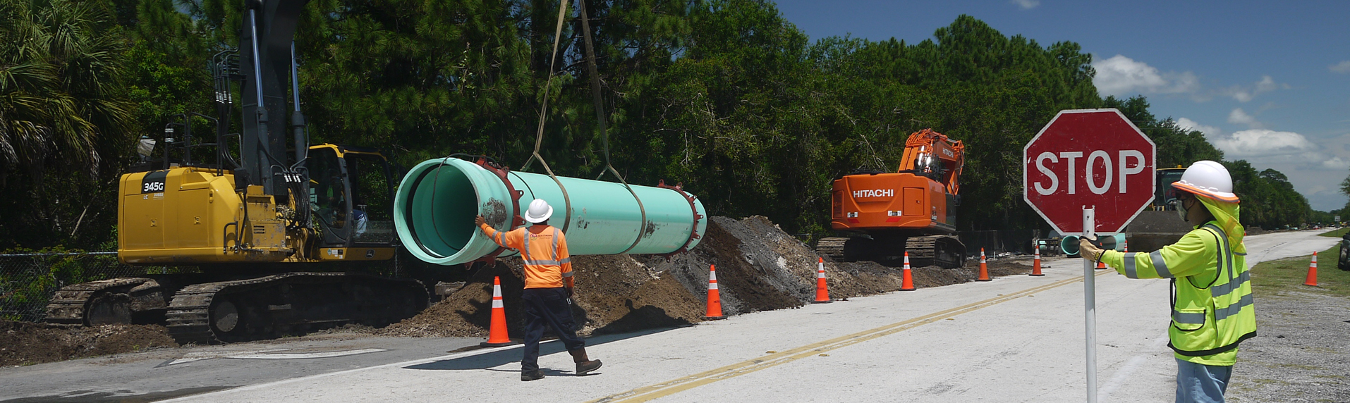 A flagger stops traffic while a pipe is lowered into the trench.